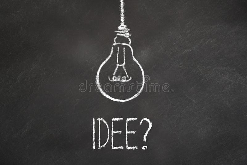"""Текст """"Idee """"мела и лампочка на доске Перевод: """"Идея """" бесплатная иллюстрация"""