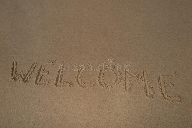 Текст & x22; welcome& x22; на летнем времени песка пляжа стоковые фото