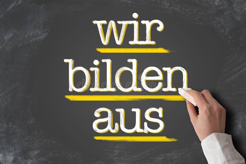 Текст WIR BILDEN AUS, немецкий ибо мы тренирует подмастерьев, на доске стоковое изображение