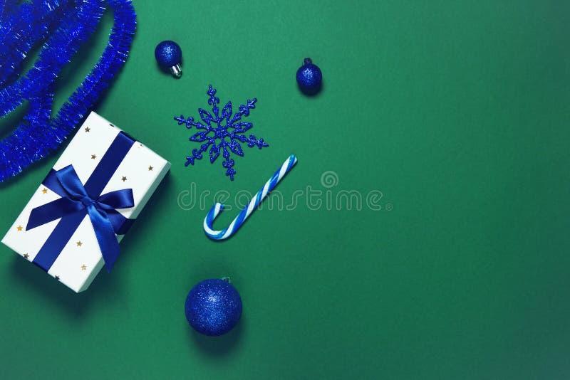Текущая коробка, завернутая темно-голубой лентой, декоративными шариками и леденцом на фоне зеленой бумаги Рождественский подарок стоковая фотография