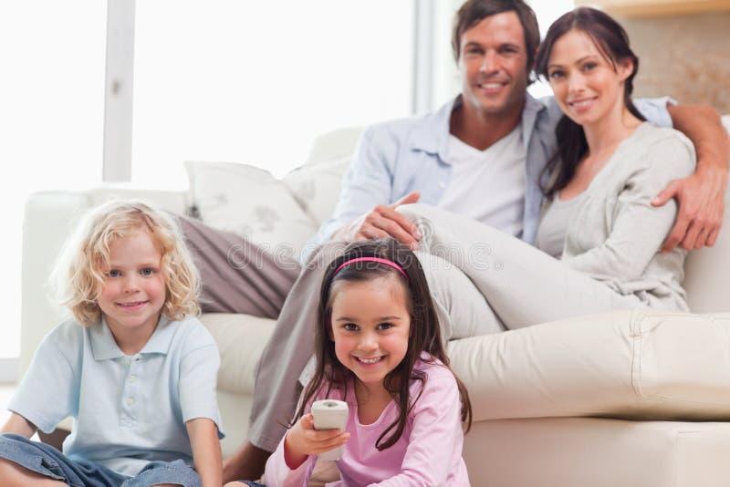 Телевидение симпатичной семьи наблюдая стоковое фото