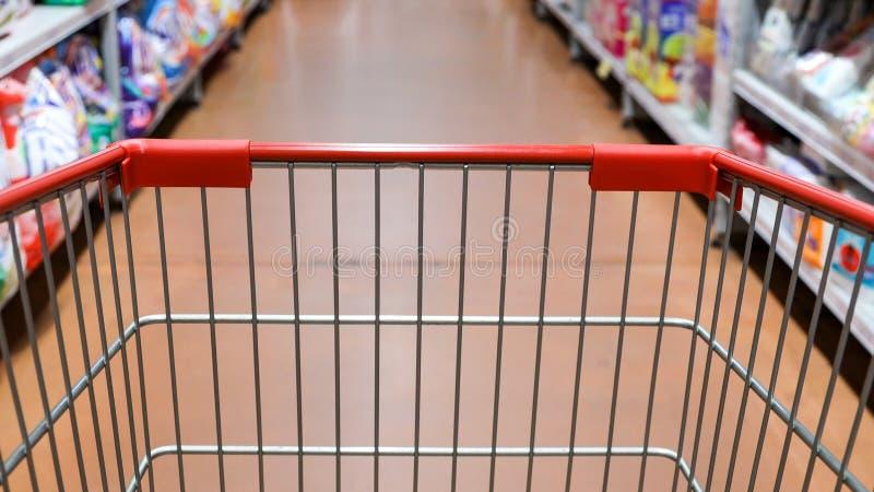 Тележка вагонетки взгляда перспективы ходя по магазинам с предпосылкой супермаркета запачканной проходом стоковое изображение