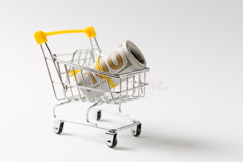 Тележка нажима бакалеи супермаркета для ходить по магазинам с желтыми элементами на ручке с пачкой наличных денег банкноты денег  стоковое фото