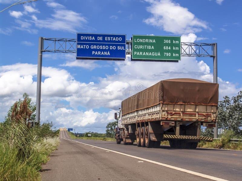 Тележка на дороге пересекает границу между государствами Mato Grosso и Parana, со знаками показывая расстояния в километрах t стоковая фотография