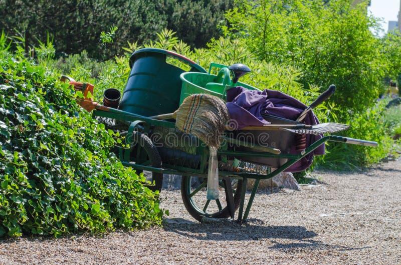Тележка сада с веником, грабл, моча чонсервной банкой и ведрами в bo стоковое изображение