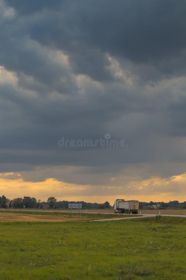 Тележка управляет на дороге сельской местности на бурном вечере лета стоковая фотография rf
