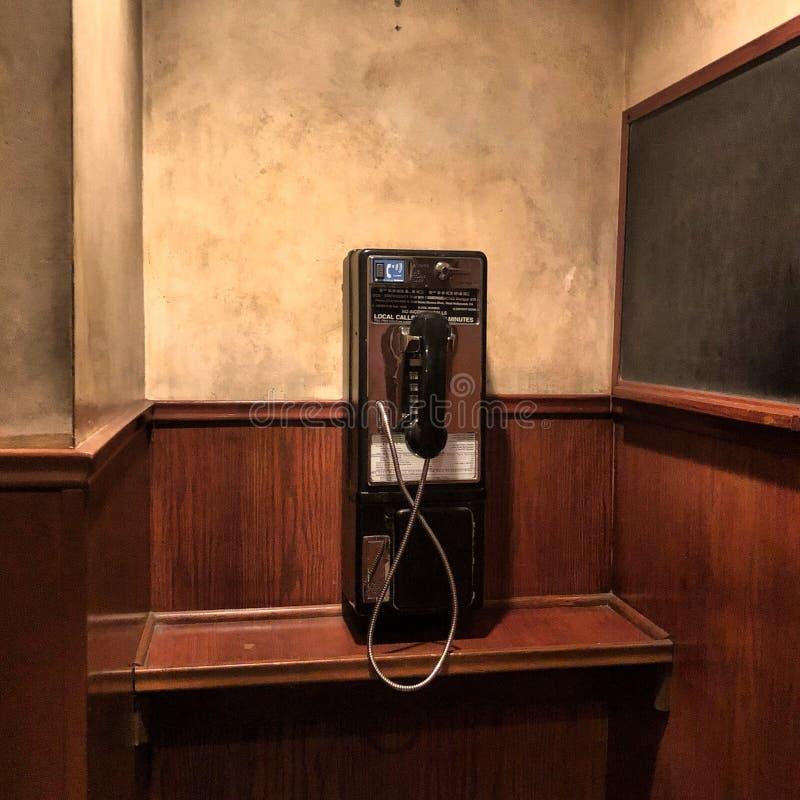 Телефон-автомат на коричневой стене стоковые фотографии rf