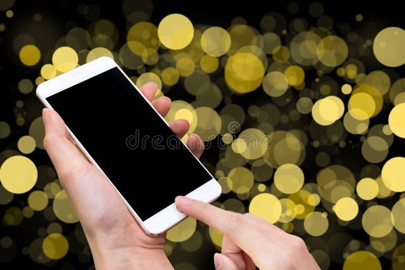 Телефон владением женщины умные и кнопка касания вручную с пустым экраном для рекламы, желтой нерезкости Bokeh и абстрактной пред стоковая фотография rf