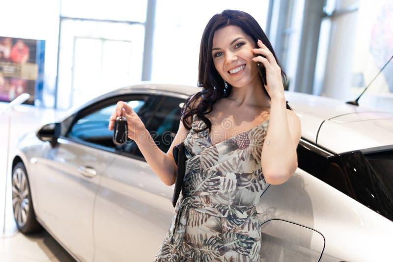 Телефон восхитительного брюнета говоря и possing около ее нового автомобиля в выставочном зале дилерских полномочий стоковое фото