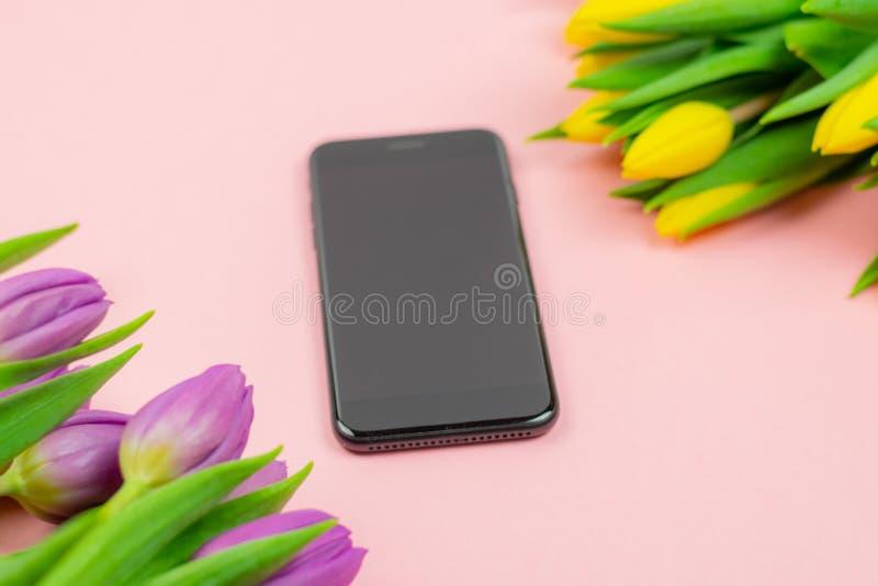 Телефон и тюльпаны на розовой предпосылке стоковая фотография