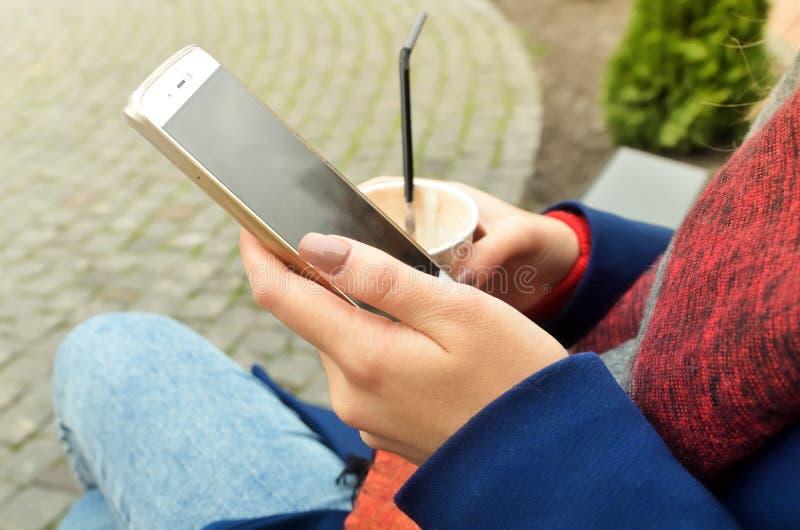 Телефон и чашка кофе в women& x27; руки s стоковая фотография rf