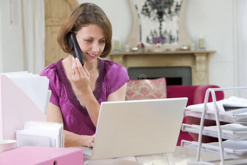 телефон компьтер-книжки говоря используя женщину стоковая фотография