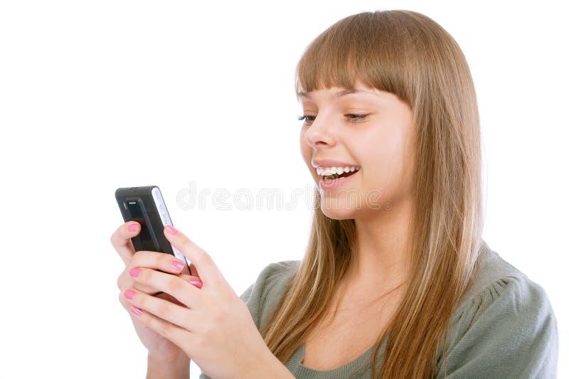 телефон сообщения девушки читает усмехаться стоковое фото