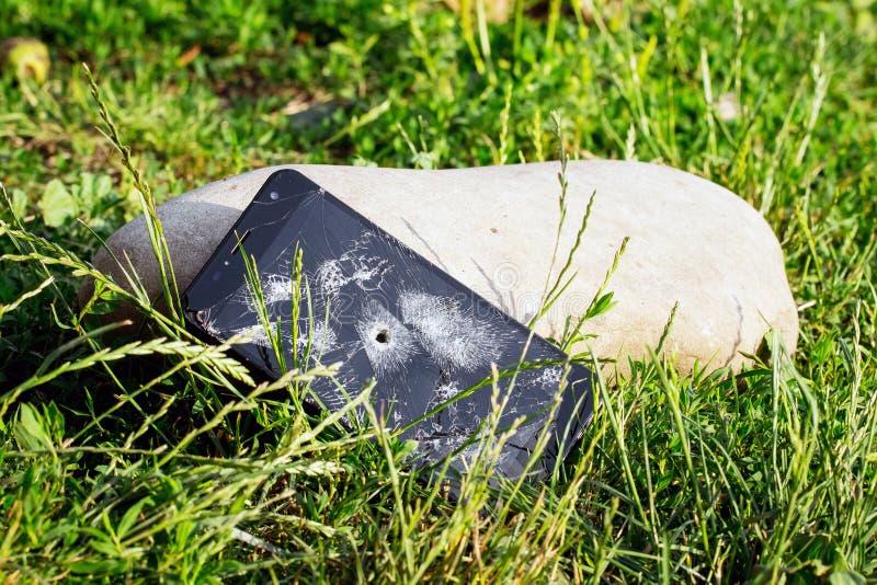 Телефон со сломленным экраном касания и отверстием от пули в траве около большого stone_ стоковое фото rf