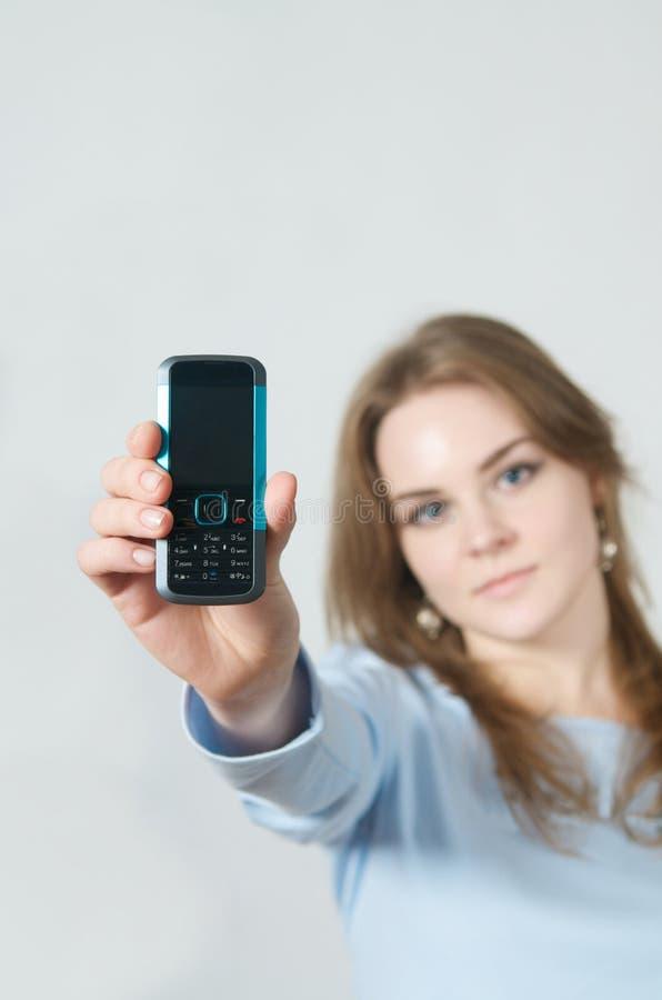телефон удерживания девушки клетки стоковое изображение rf