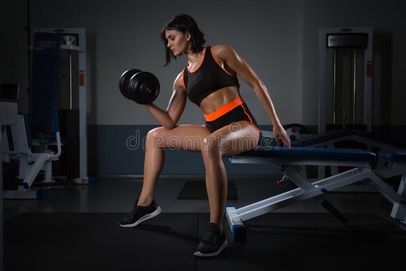 телохранителя гантели работая женщину Весы мышечной девушки брюнет поднимаясь сняли на спортзале на темноте стоковые изображения rf