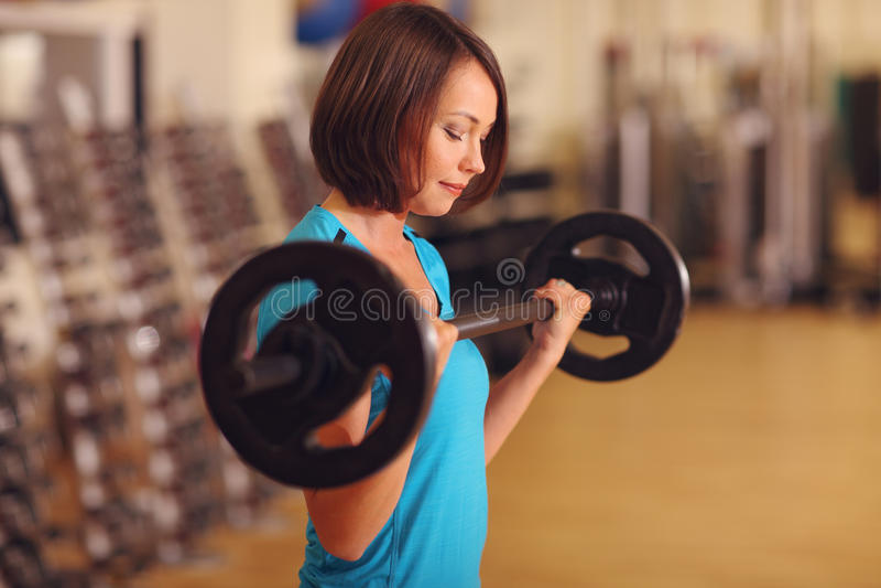 телохранителя женщина работая с штангой в классе фитнеса Женская разминка в спортзале с штангой стоковые фото