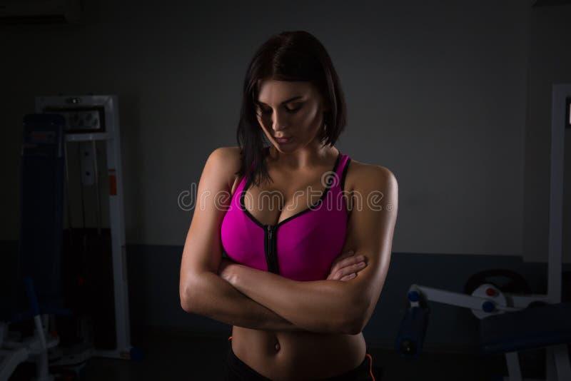 Тело красивой пригонки тонкое тонкое тонизированное женское скачет спортсмен веревочки на темноте стоя уверенно стоковое изображение rf