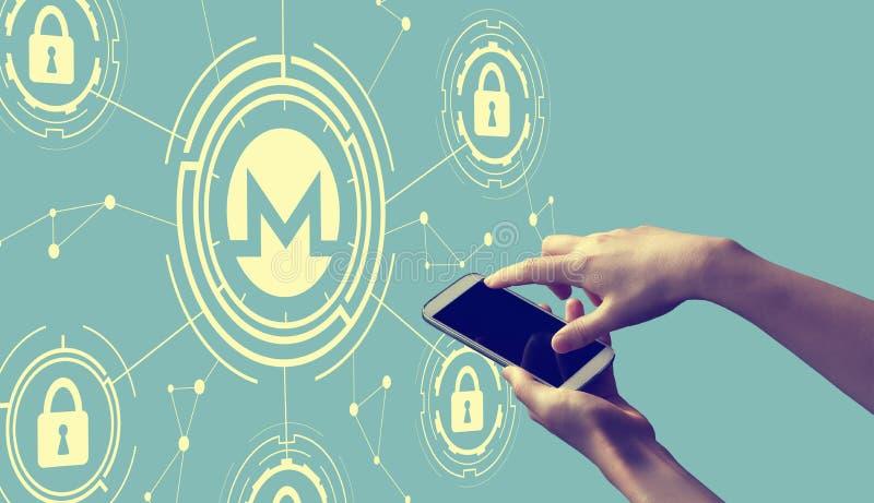 Тема безопасностью cryptocurrency Monero со смартфоном удерживания человека стоковое фото rf