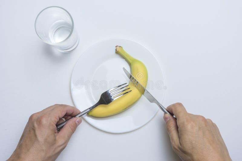 Тема здоровой еды: руки людей держат вилку и нож, банан и горохи в форме улыбки на плите на белом стоковые изображения rf