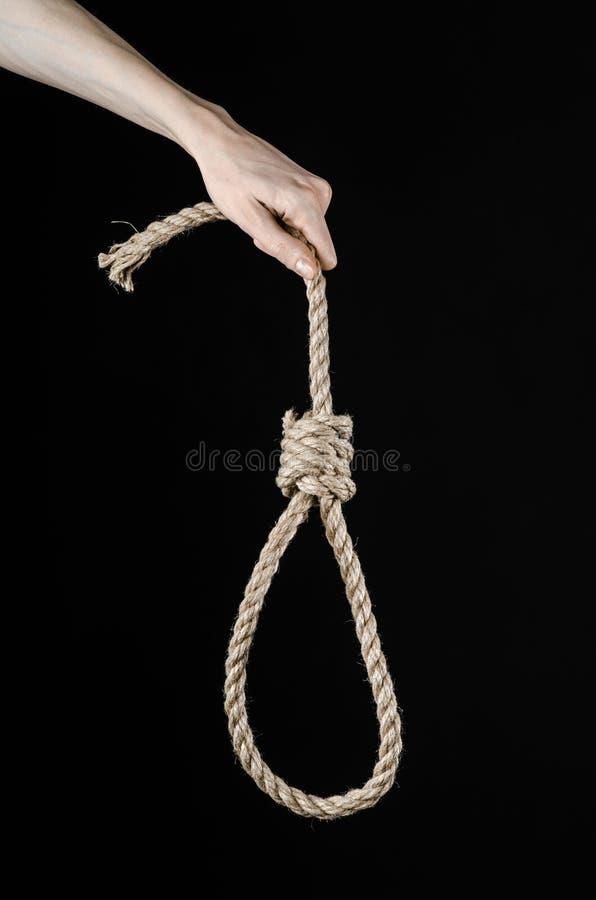 Тема линчевания и суицида: рука человека держа петлю веревочки для висеть на черноте изолировала предпосылку стоковые фотографии rf