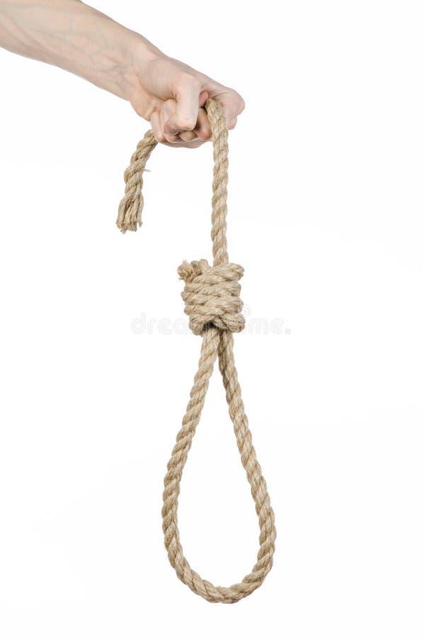 Тема линчевания и суицида: рука человека держа петлю веревочки для висеть на белизне изолировала предпосылку стоковое изображение