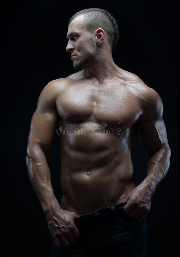 Тема культуриста и прокладки: красивый при нагнетенный человек мышц нагой представляя в студии на темной предпосылке стоковое фото