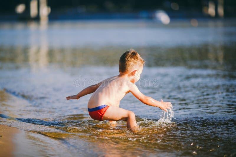 Тема лето и остатки около воды Немногое радостный кавказский смешной мальчик играет и наслаждается в реке E стоковые фото