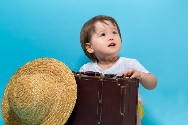 Тема перемещения мальчика малыша с suitecase и шляпой стоковые фото