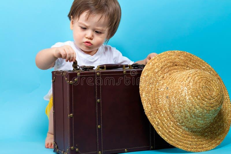 Тема перемещения мальчика малыша с suitecase и шляпой стоковые изображения rf