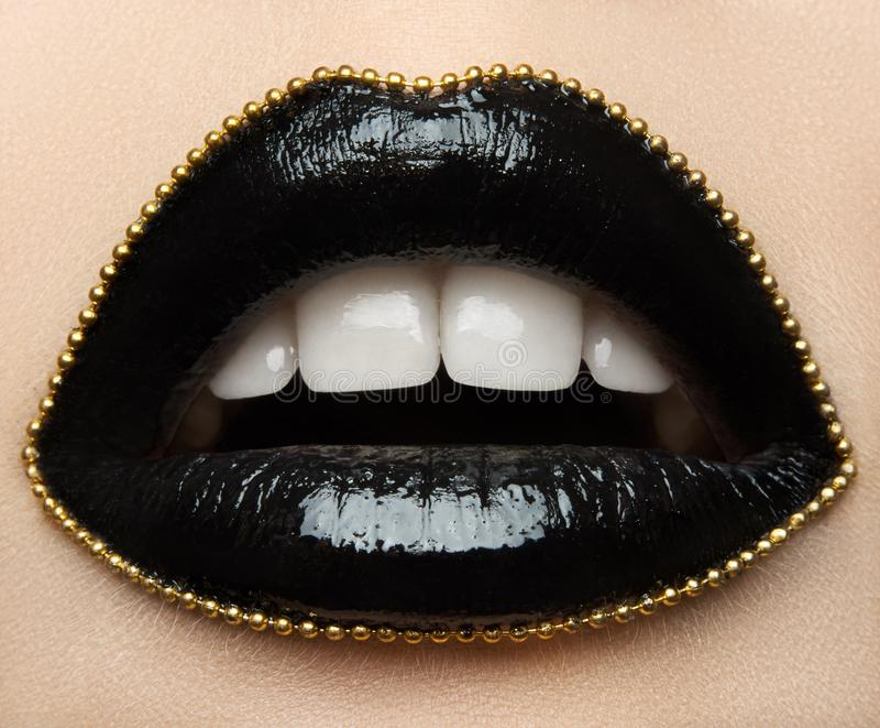 Тема состава макроса и конца-вверх творческая: красивые женские губы с черной губной помадой и цепью золота вдоль контура стоковые изображения rf