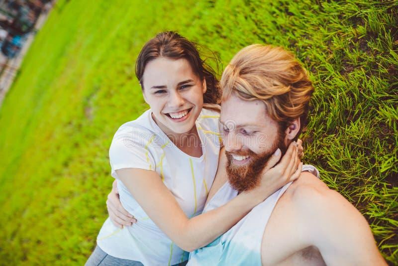 Тема спорт и здоровый образ жизни Пара молодого человека и женщины отдыхает лежать на их задних частях на зеленой траве, лужайке  стоковые изображения