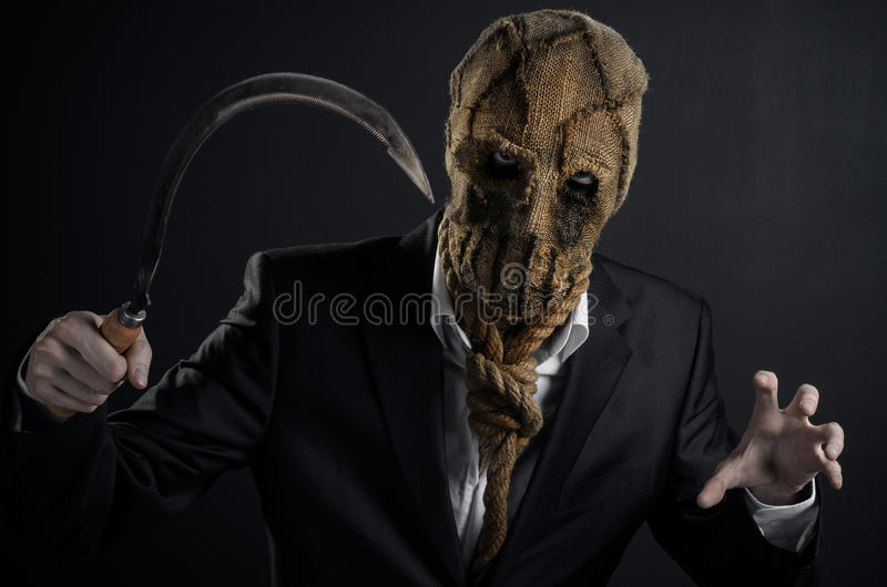 Тема страха и хеллоуина: зверская убийца в маске держа серп старой на темной предпосылке в студии стоковое фото