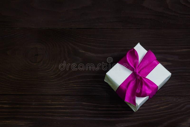 Тема торжеств и подарков: исключительный подарок упаковал в белой коробке с фиолетовым подарком ленты, красивых и дорогих на темн стоковые фотографии rf