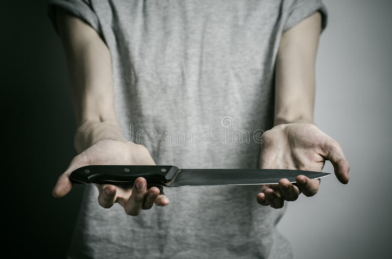 Тема убийства и хеллоуина: человек держа нож на серой предпосылке стоковая фотография rf