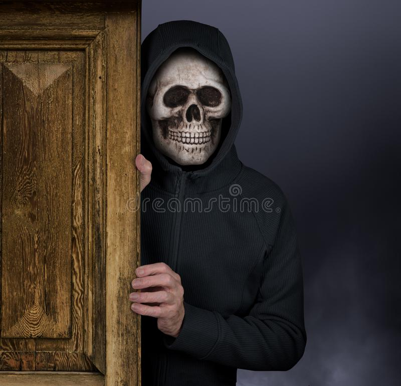 Тема хеллоуина человека с маской черепа приветствуя к преследовать дому стоковое изображение