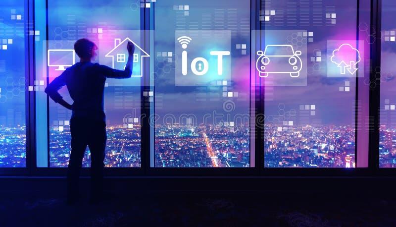 Тема IoT с человеком большими окнами вечером стоковое фото