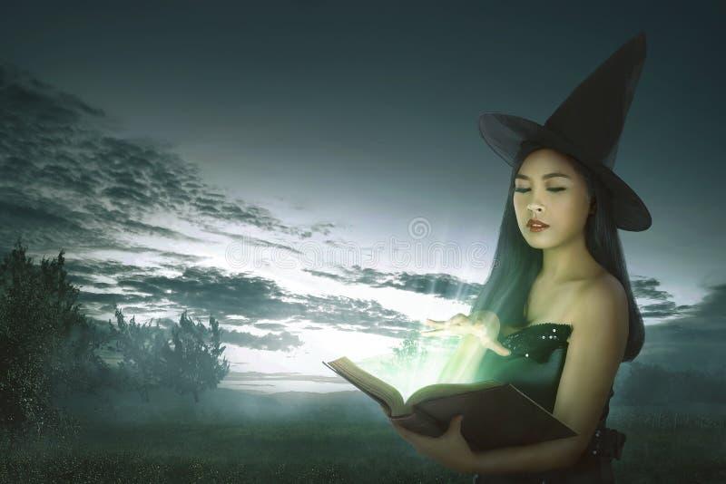 Темная азиатская женщина ведьмы с книгой произношения по буквам стоковая фотография rf