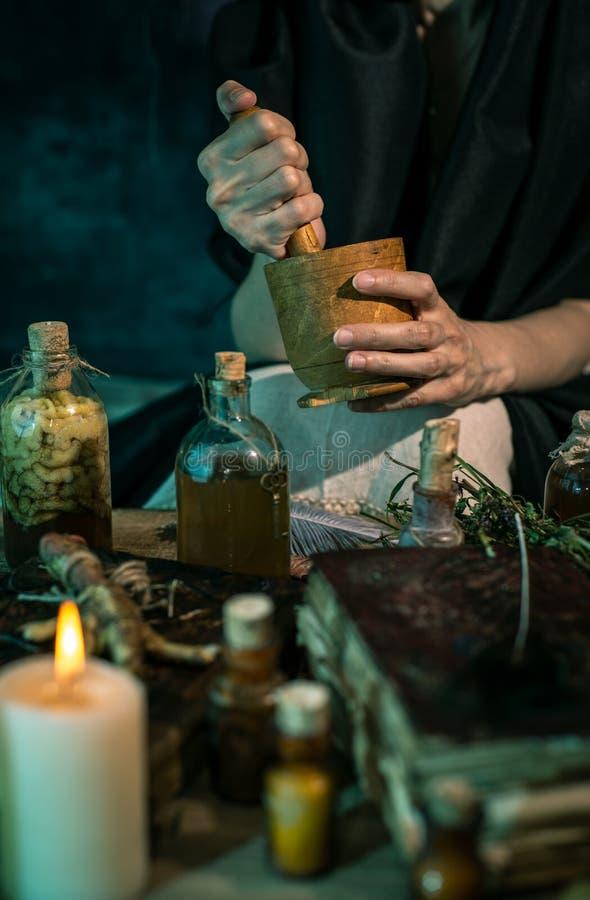 Темная ведьма на работе: женщина черной магии делает witchery путем смешивать травы, бросающ произношения по буквам, бежать волше стоковая фотография rf