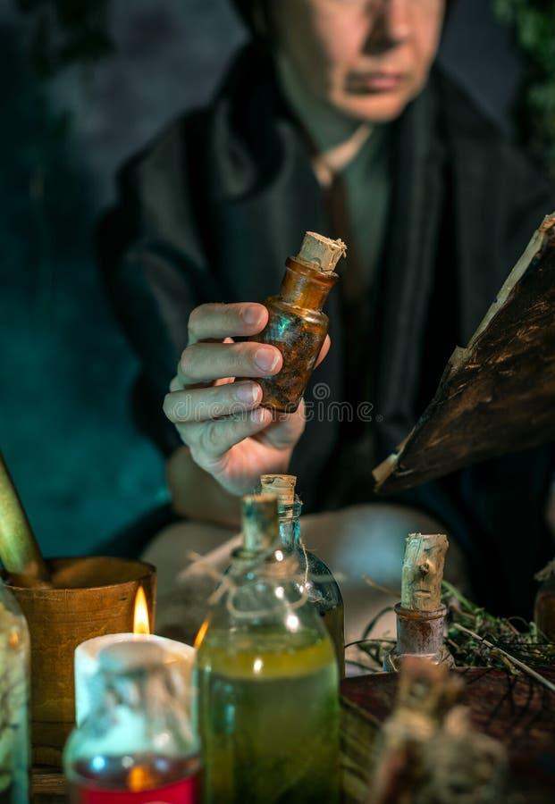 Темная ведьма на работе: женщина черной магии делает witchery путем смешивать травы, бросающ произношения по буквам, бежать волше стоковое изображение