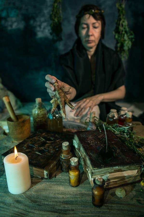 Темная ведьма на работе: женщина черной магии делает witchery путем смешивать травы, бросающ произношения по буквам, бежать волше стоковые фото