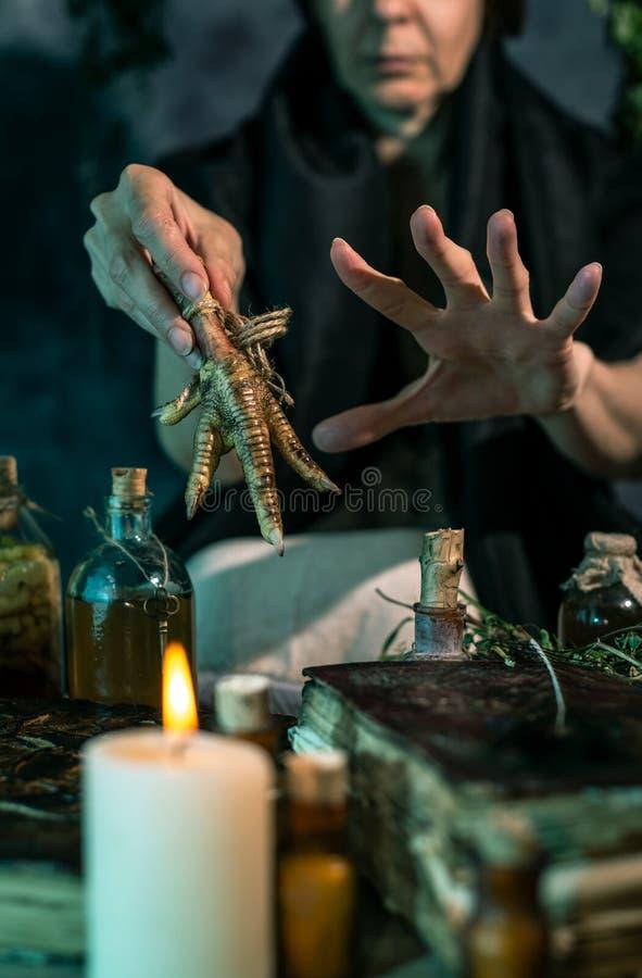 Темная ведьма на работе: женщина черной магии делает witchery путем смешивать травы, бросающ произношения по буквам, бежать волше стоковая фотография