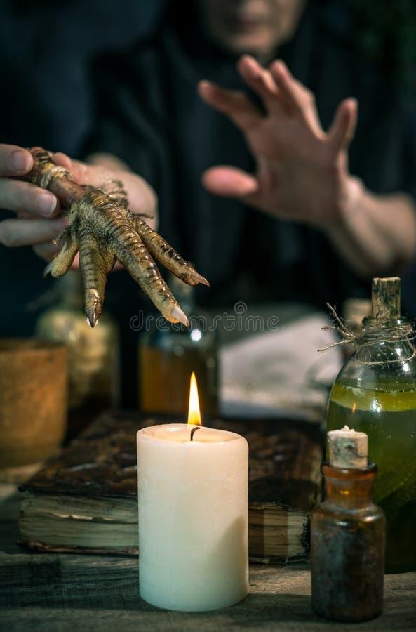 Темная ведьма на работе: женщина черной магии делает witchery путем смешивать травы, бросающ произношения по буквам, бежать волше стоковое изображение rf