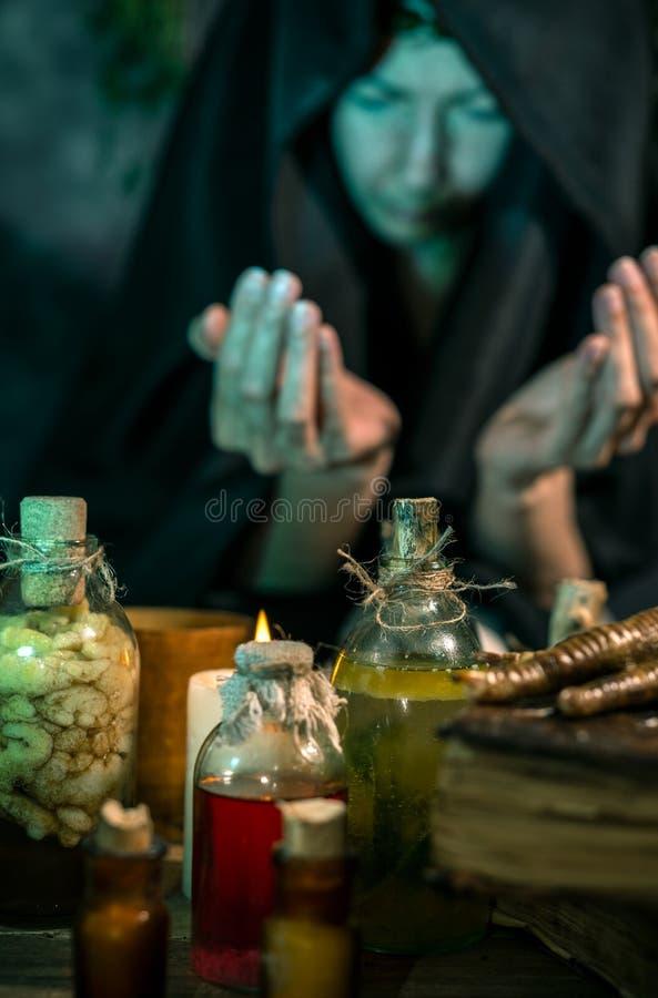 Темная ведьма на работе: женщина черной магии делает witchery путем смешивать травы, бросающ произношения по буквам, бежать волше стоковое фото