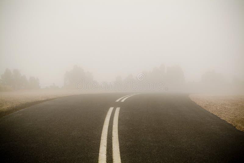 темная дорога тумана стоковое изображение