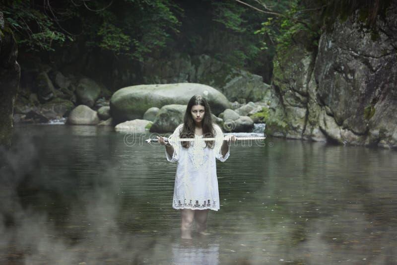 Темная девушка с шпагой в потоке горы стоковое фото rf