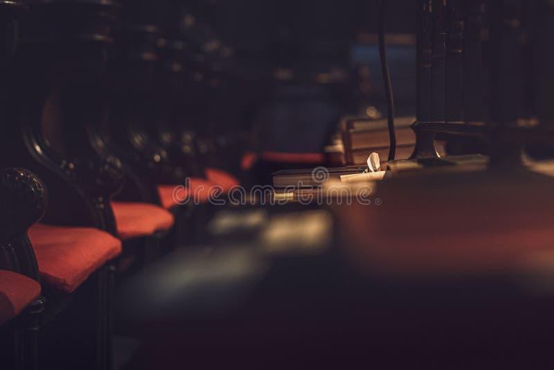 Темная и унылая съемка одиночной библии в фокусе в большом соборе стоковые фото