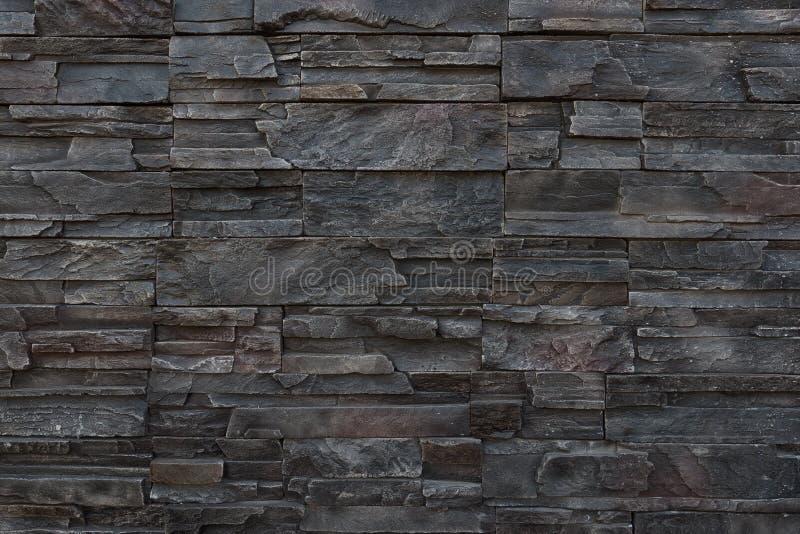 Темная предпосылка текстуры каменной стены стоковое фото