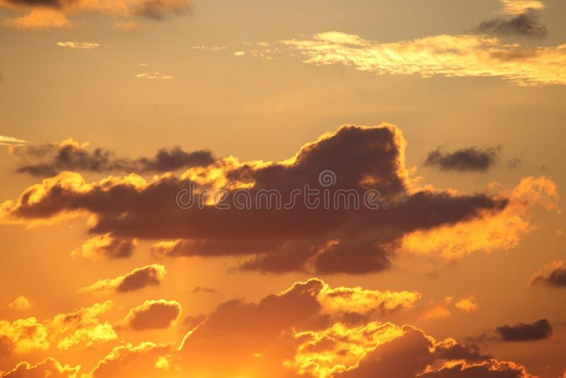 Темное облако над золотым заходом солнца стоковая фотография