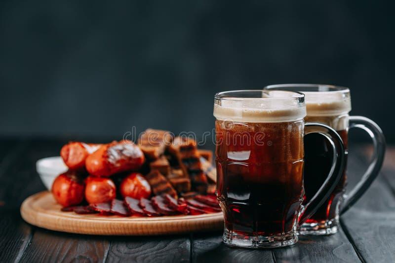 Темное установленные пиво и аппетитные закуски пива Таблица с 2 кружками  стоковое фото